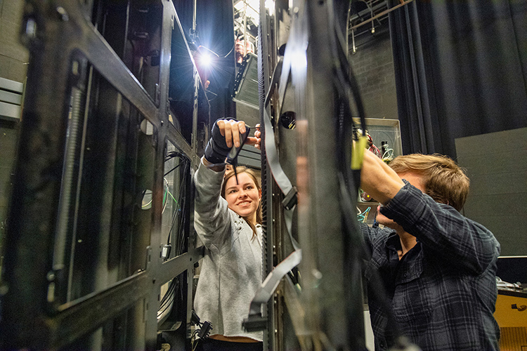 "Middle Tennessee State University media arts students Sydney Penn, left, and Liam Nelson, right, deconstruct LED video display panels for use on the set of MTSU Theatre's production of ""Joseph and the Amazing Technicolor Dreamcoat"" on campus on March 15, 2018. (MTSU file photo by Andy Heidt)"