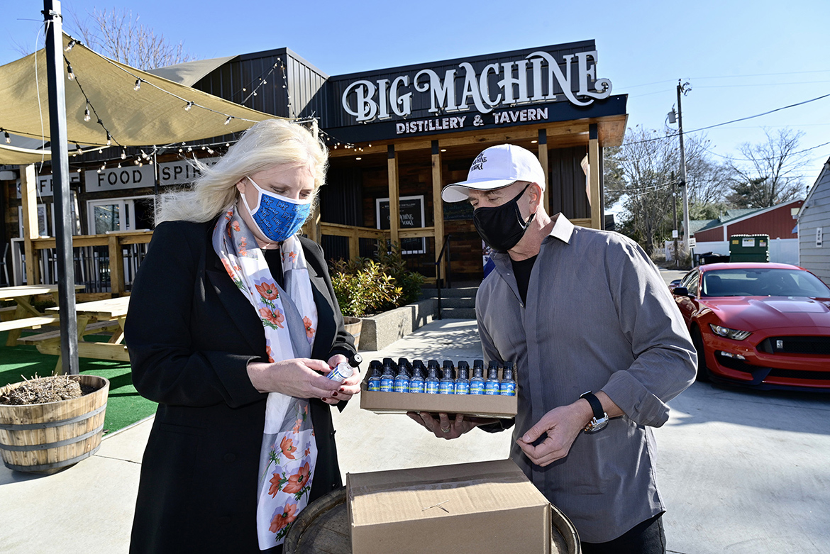 Beverly Keel, dean of MTSU's College of Media and Entertainment, looks at a bottle of Lightning Hand Sanitizer given to her by Mark Borchetta, executive vice president of Big Machine Vodka outside the distillery's Nashville, Tenn., location Friday, Jan. 15. MTSU contracted with Big Machine for 6,000 personal-size bottles of sanitizer for students living in on-campus residence halls. (MTSU photo by Andy Heidt)