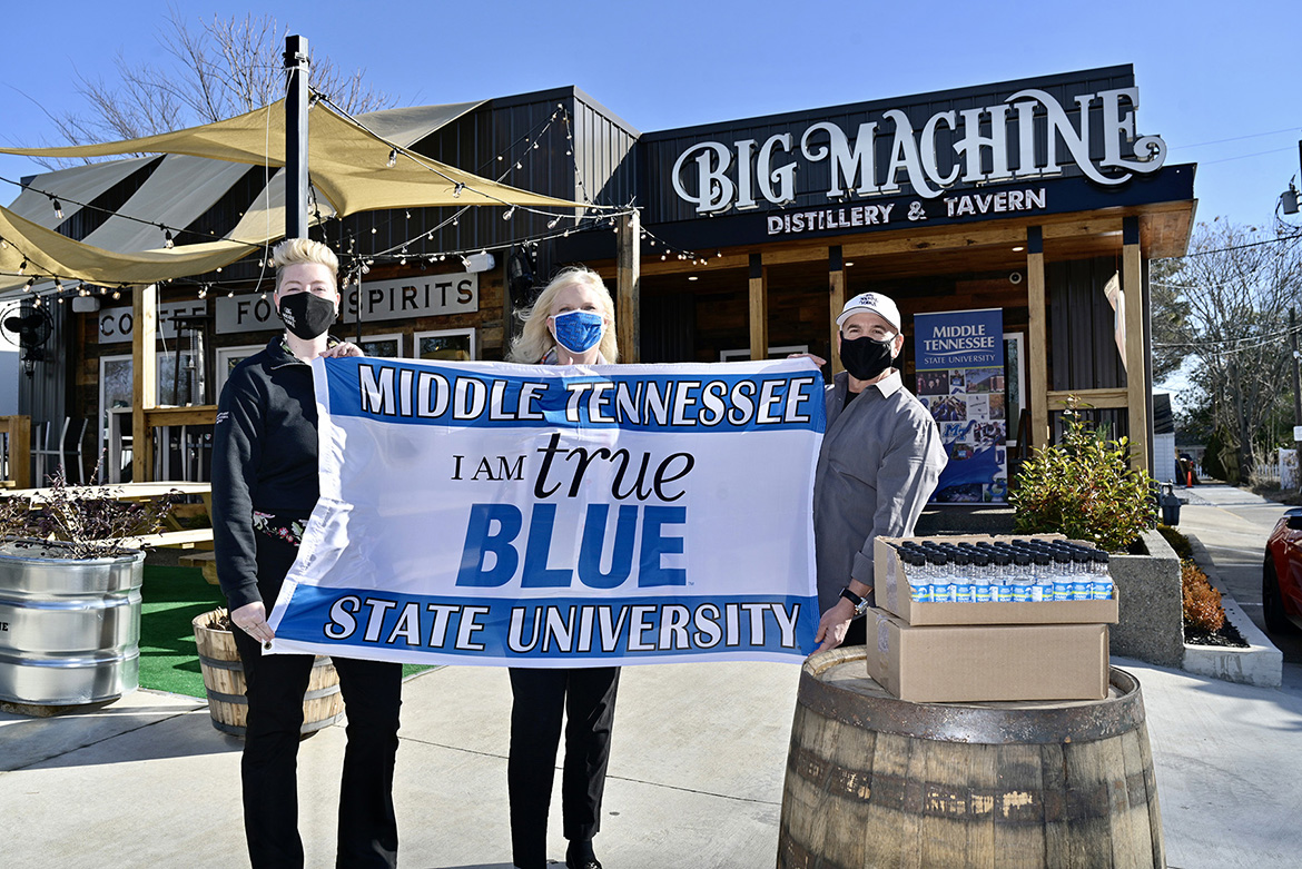 Kiley Judge, general manager of Big Machine Tavern; Beverly Keel, dean of MTSU's College of Media and Entertainment; and Mark Borchetta, executive vice president of Big Machine Vodka, display an MTSU banner at a presentation Friday, Jan. 15, at the distillery's Nashville, Tenn., location as MTSU took receipt of 6,000 personal-size bottles of sanitizer made by Big Machine for students living in on-campus residence halls. (MTSU photo by Andy Heidt)