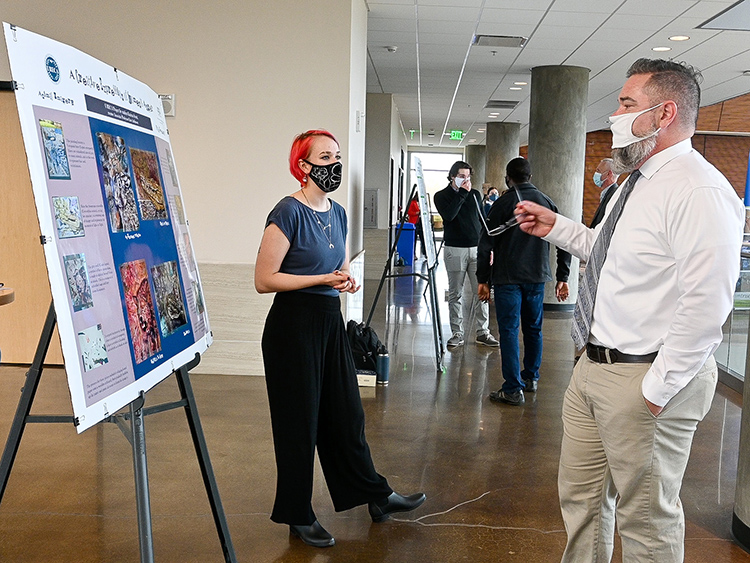 Katrina Scott, left, a Middle Tennessee State University undergraduate student majoring in art and design, presents her research to David Butler, right, vice provost for research and dean of the College of Graduate Studies, at the MTSU Undergraduate Research Open House event held Nov. 10, 2020, in the Science Building mezzanine on campus. (MTSU photo by Stephanie Barrette)