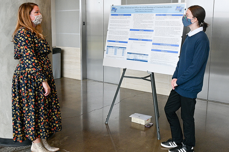 Jamie Burriss, left, the program manager of Middle Tennessee State University's Office of Research and Sponsored Programs, listens to undergraduate student Dara Zwemer, right, present her research about law enforcement at the MTSU Undergraduate Research Open House event held Nov. 10, 2020, in the Science Building mezzanine on campus. (MTSU photo by Stephanie Barrette)