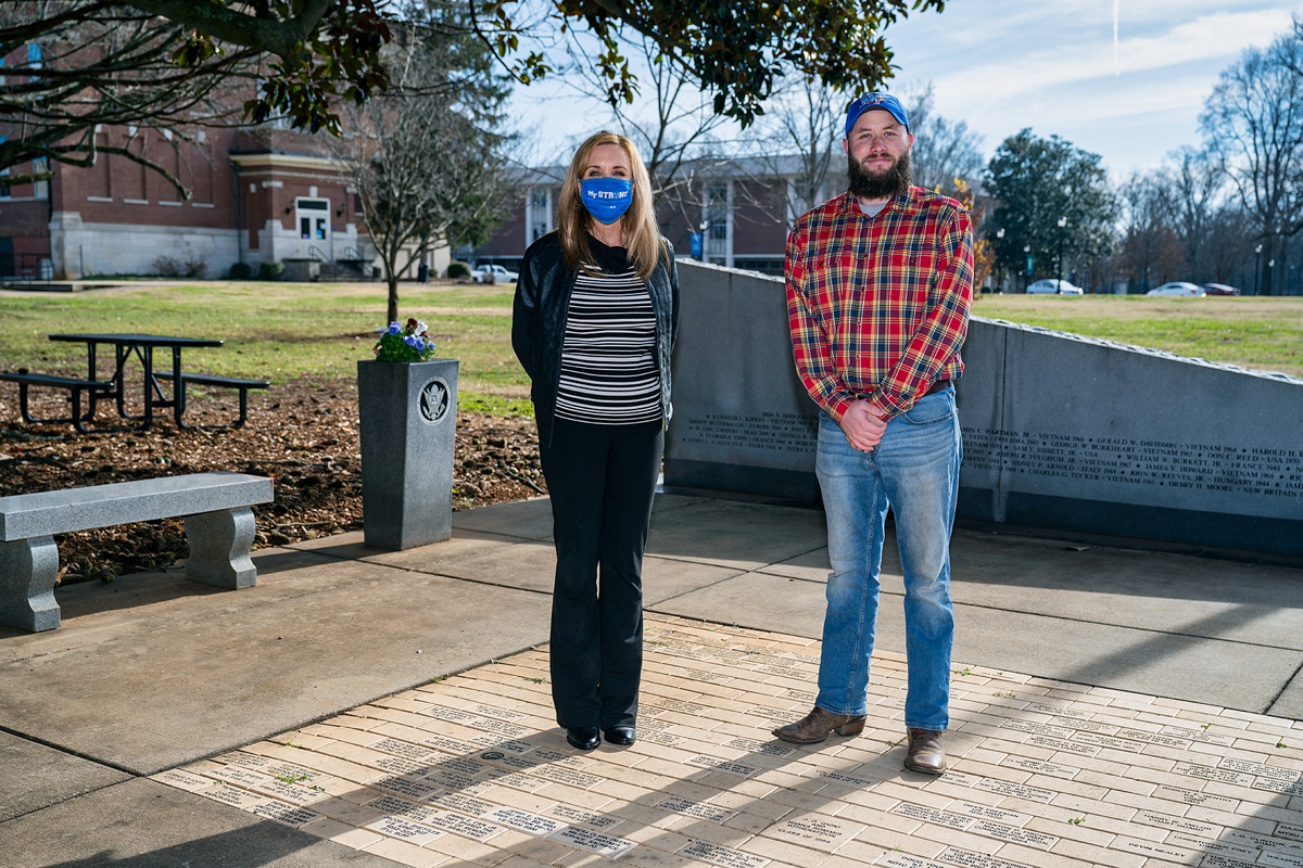 Hilary Miller, left, director of MTSU's Charlie and Hazel Daniels Veterans and Military Family Center, and student veteran Orrin Farmer stand at the Veterans Memorial site outside the Tom H. Jackson Building recently. Farmer is one of dozens of military-connectred students assisted by two grants in 2020, helping them out during the COVID-19 pandemic. He is an aerospace professional pilot major from Casper, Wyoming. (MTSU photo by Andy Heidt)