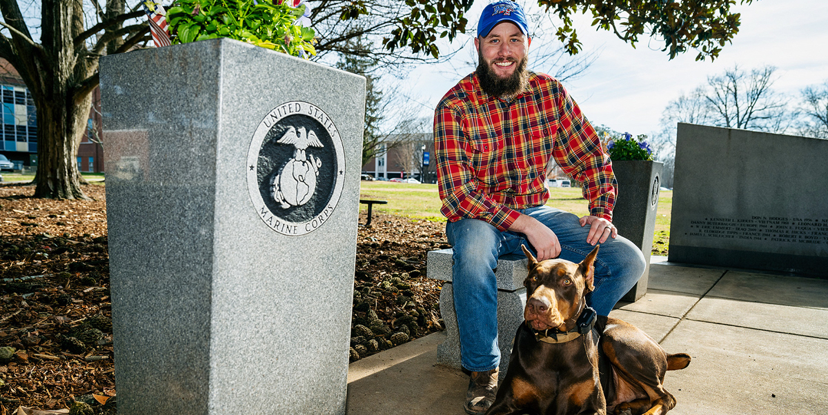 Along with his dog Loki, MTSU student veteran Orrin Farmer visits the MTSU Veterans Memorial site outside the Tom H. Jackson Building on the west side of campus recently. An aerospace professional pilot major, Farmer, who was in the U.S. Marine Corps for four years, was one of dozens of military-connected students who received assistance from a United Way of Rutherford and Cannon Counties $10,000 grant in 2020, providing help to he and his wife during the stressful COVID-19 pandemic. (MTSU photo by Andy Heidt)