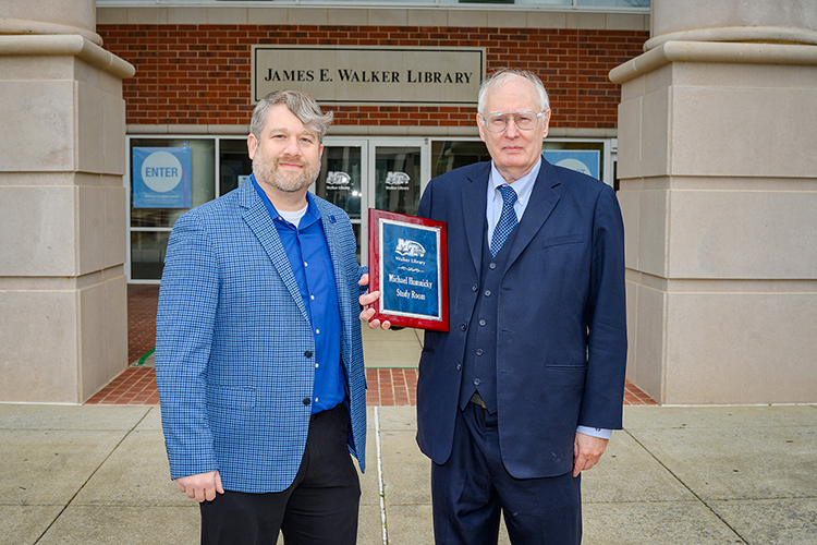 Paul Wydra, left, MTSU's director of development initiatives, poses with long-time donor Michael Humnicky and the plaque designating the study room named in his honor at the James E. Walker Library. (MTSU Photo by J. Intintoli)