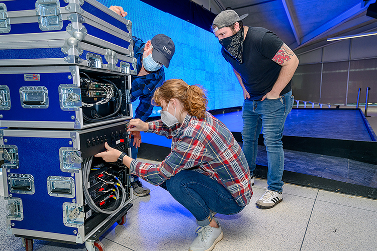 MTSU student Hannah Humphress, a Knoxville, Tenn., senior majoring in audio production, adjusts a connector for the custom LED video wall behind the stage of the university's new Chris Young Cafe in preparation for a special livestreamed grand opening on Wednesday, Jan. 27. Looking on are, at left, Frank Baird, assistant professor of audio production and the cafe's new director, and Jon White, a graduate teaching assistant in the Department of Recording Industry's Master of Fine Arts in Recording Arts and Technologies Program. Chris Young, a former MTSU student turned multiplatinum country entertainer, donated $50,000 to help renovate the 1963-era cafeteria into a teaching and rehearsal space and performance venue for the College of Media and Entertainment. (MTSU photo by J. Intintoli)