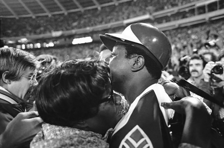 Hank Aaron, surrounded by reporters and photographers, hugs his mother, Estella Aaron, after hitting his 715th career home run in Atlanta-Fulton County Stadium on April 8, 1974, to break Babe Ruth's record. (Baseball History Comes Alive)