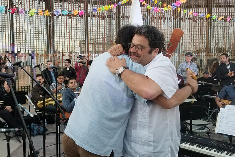 """Sunlight shines through the barrier as musicians Arturo O'Farrill, left, and Jorge Francisco Castillo hug after performing at the border wall in Tijuana, Mexico, in this May 2018 file image provided by makers of the documentary """"Fandango at The Wall."""" (file image courtesy of FandangoWall.com)"""