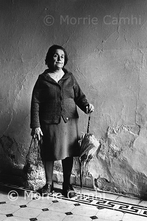 "Documentary photographer Morrie Camhi's image of ""Serina Matsas, at home, Ioannina, 1980"" depicts a woman standing in a hallway with her woven shopping bag and an umbrella in Ioannina, Greece, part of Camhi's ""Faces and Facets: The Jews of Greece"" collection. This photo is among those in a new exhibit in MTSU's Baldwin Photographic Gallery, ""An Eye Towards Justice,"" on display through Thursday, April 15. The exhibit and Camhi's work also are the subject of an online panel discussion with MTSU faculty experts set for Tuesday, March 30, at 6:30 p.m. Central. (photo by Morrie Camhi)"