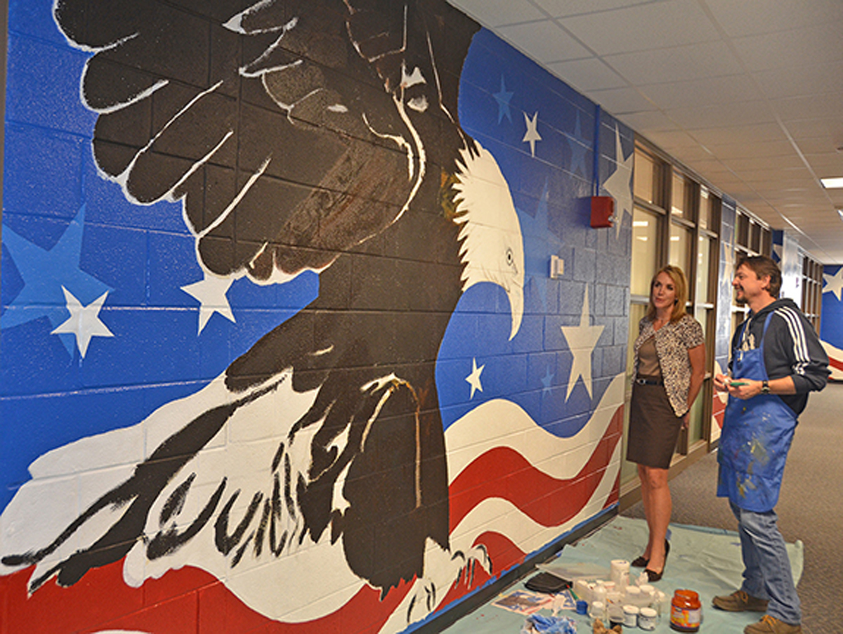 Hilary Miller, left, director of MTSU's Charlie and Hazel Daniels Veterans and Military Family Center, discusses the eagle mural with alumnus Randy Purcell, a professional artist, in the Keathley University Center. Purcell is painting a 70-foot section of the hallway outside the center. The center is home to 1,000 student veterans and family members who are welcome to participate in monthly virtual Roll Call veterans speaker events and more. (MTSU file photo by Randy Weiler)