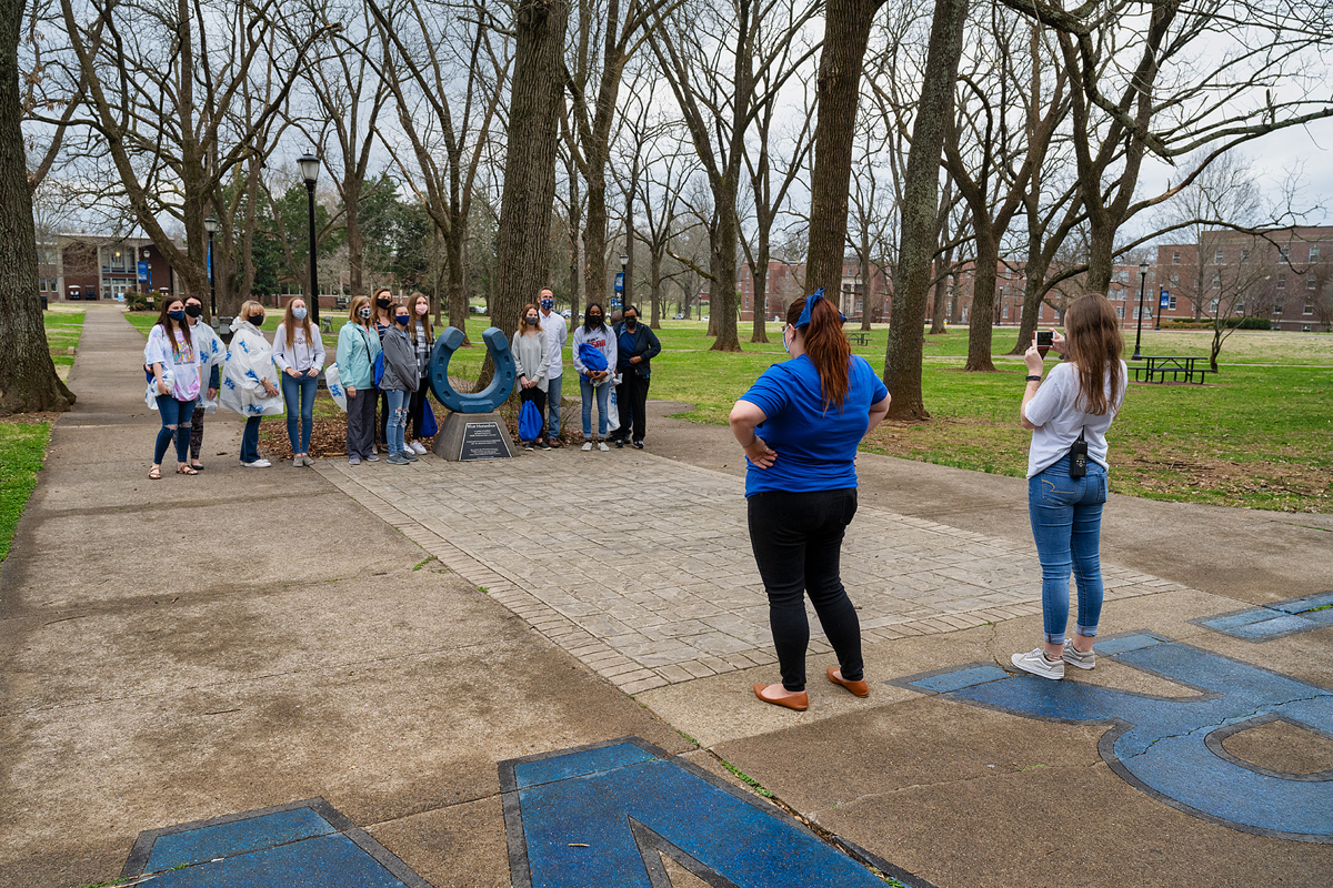 Miura Rempis, left foreground, and Ashley Conser take a recent in-person MTSU daily campus tour group to the Blue Horseshoe in Walnut Grove near Peck Hall for a photo opportunity. The tours, which are led by Blue Elite students, last approximately one hour. (MTSU photo by Andy Heidt)