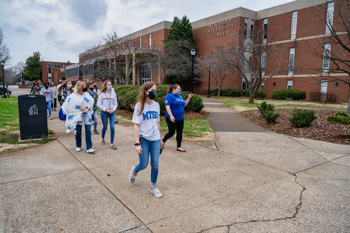 MTSU student tour guides Ashley Conser, left, and Miura Rempis lead a recent in-person daily campus tour, as the group walks past Keathley University Center in the heart of campus. Tours are scheduled four times daily and some Saturdays by the Admissions Office. Masks and social distancing are part of the COVID-19 safety protocols being followed. (MTSU photo by Andy Heidt)