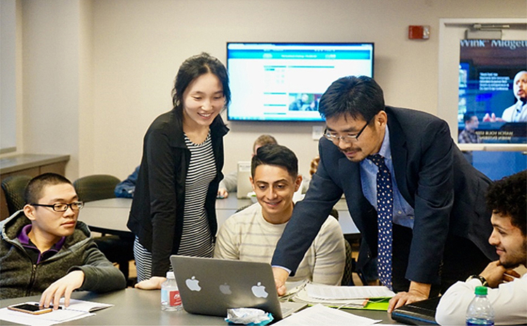 MTSU Economics and Finance professor Kevin Zhao, standing at right, advises students in his Spring 2018 TVA Investment Challenge class inside the Business and Aerospace Building. The annual competition allows college students from universities throughout the region an opportunity to manage a real stock portfolio to hone their analytical skills. (Submitted photo)