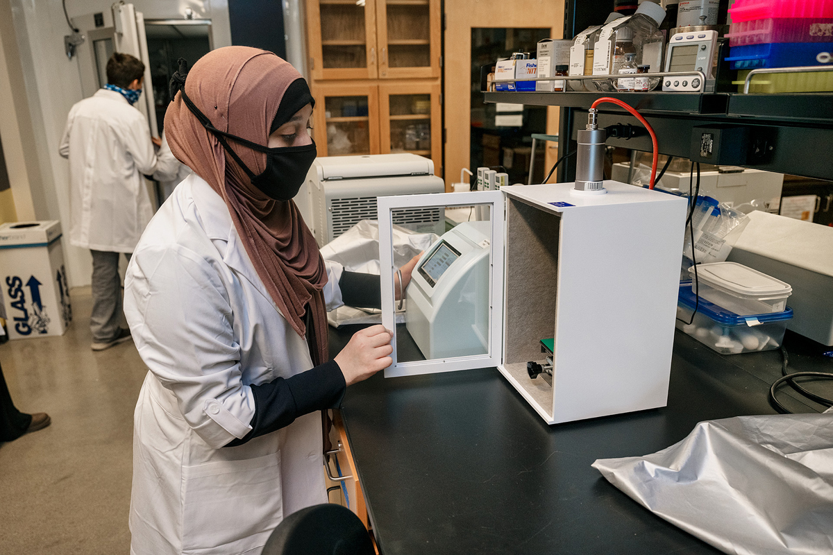 Zaynab Alnassari inspects equipment she uses in an MTSU biology lab in the Science Building. She is among 14-year-old triplets doing dual enrollment studies in biology at MTSU. They are all on a pre-med pathway. (MTSU photo by Andy Heidt)