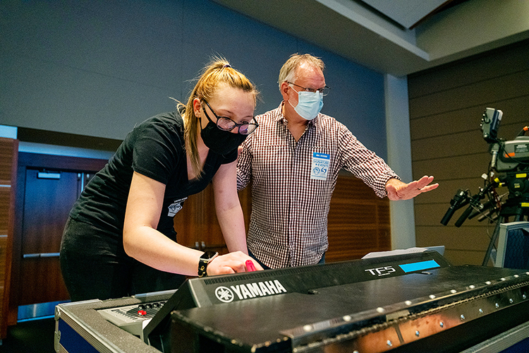 """Sam Hopewell, left, a senior audio production major from Rockford, Illinois, works on the mixing board while Department of Recording Industry professor Frank Baird gestures to another crew member on stage during setup Wednesday, March 24, for the Briston Maroney concert in MTSU's Student Union ballroom. Hopewell, whose minor is in theatre, was one of nearly 50 students from two different colleges — and three departments — who collaborated to present MTSU's first in-person, large-scale """"Signature Event"""" since 2019. (MTSU photo by Andy Heidt)"""