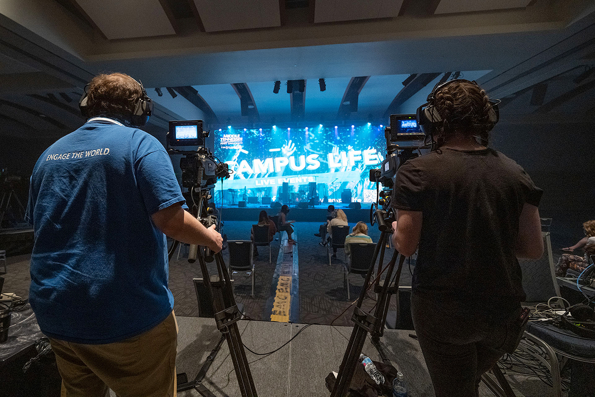 """MTSU senior video and film production majors Nathaniel Muncie, left, of Johnson City, Tennessee, and Brea Robbins of Cookeville, Tennessee, focus on the stage, featuring a student-constructed 40-foot-by-18-foot video wall, on Wednesday, March 24, between acts at the Briston Maroney concert in the Student Union ballroom. The Department of Media Arts students in MTSU's advanced multi-camera TV production course were among nearly 50 students from two different colleges — and three departments — who collaborated to present MTSU's first in-person, large-scale """"Signature Event"""" since 2019. (MTSU photo by Cat Curtis Murphy)"""