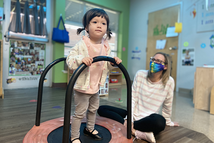 """One of the little learners at MTSU's Ann Campbell Early Learning Center holds to a bar for balance while playing in the center's Green Room for 1- to almost 3-year-olds as teacher Kristy Kirby watches and smiles alongside. The nonprofit, inclusive preschool, an arm of MTSU's College of Education, is holding a drive-thru version of its annual """"Saddle Up"""" fundraiser on Saturday, April 17. For more information, visit https://www.mtsu.edu/acelearningcenter/saddleup.php. (Photo courtesy of the Ann Campbell Early Learning Center at MTSU)"""
