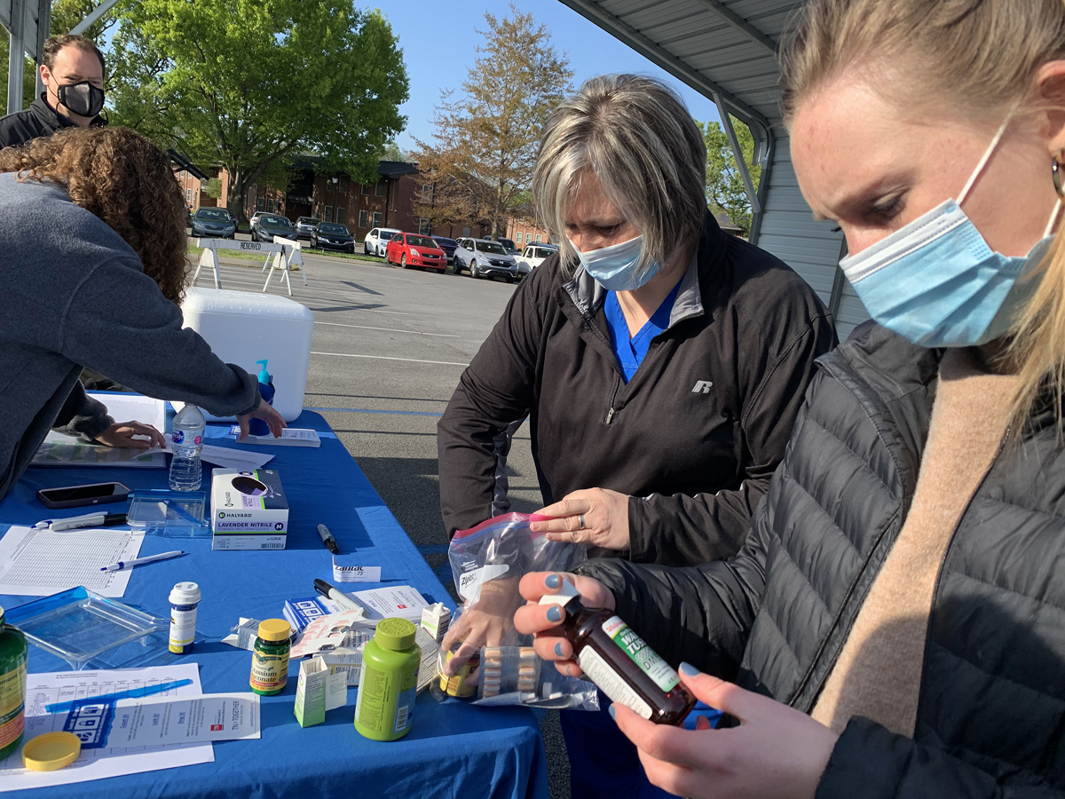 MTSU Health Services nurse Heather Ashby, second from right, empties some of her family's old medications out for university officials to count as part of the spring MTSU Drug Take-Back Day event Thursday, April 22, outside the Health, Wellness and Recreation Center on Blue Raider Drive. Lipscomb University fourth-year pharmacy student Abby Sparkman, right, studies a bottle of old medicine — part of 71.7 pounds collected during the 5½- hour drive before adding it to the collection list. Also pictured are Pharmacist Tabby Ragland and Rick Chapman, Health Services director. (MTSU photo by Randy Weiler)
