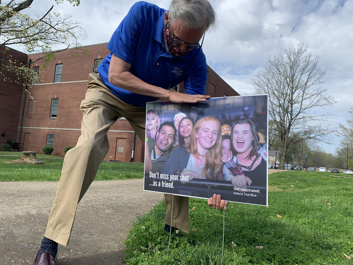 """Ed Arning, director of market development for the MTSU Division of Marketing and Communications, places yard signs near the James Union Building and other locations across campus, promoting the upcoming promotional effort for students to receive their COVID-19 vaccinations from April 12-16 in the Student Union Building's first-floor lobby. The signs had various """"Don't miss your shot"""" themes — """"as an artist, as a Blue Raider, as a friend, as a student"""" and more — to attract students' attention. (MTSU photo by Randy Weiler)"""
