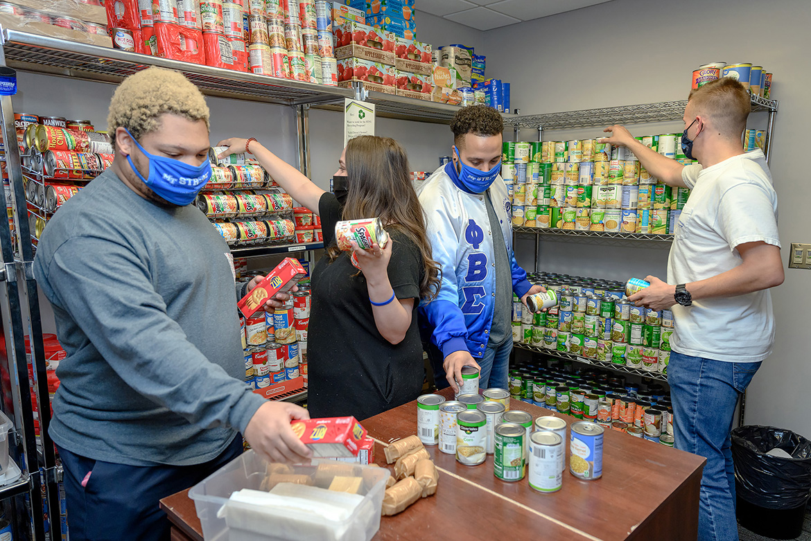 Volunteers help stock the shelves at the Student Food Pantry in the MT One Stop April 14. During Greek Week April 12-16, Fraternity and Sorority Life and the Student Government Association combined to collect more items than the pantry has received before. From left, Ryan Offutt, Greek Week Committee member; Jordan McCain, Greek Week Committee chair; Jalen Everett, National Pan-Hellenic Council president; and Alex Wissert, Interfraternity Council president. (MTSU photo by J. Intintoli)