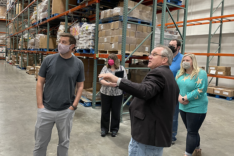 Frank Ellmo, at right in foreground, senior director of operations at Second Harvest Food Bank of Middle Tennessee, explains the nonprofit's operations to Ryan Otter, foreground left, co-director of the MTSU Data Science Institute, and some of the students in the inaugural cohort in MTSU's data science graduate certificate program during the group's April 11 visit to Second Harvest's warehouse location in Nashville, Tenn. Second Harvest provided the group access to some of its databases as part of the students' final class project. (MTSU photo by Charlie Apigian)