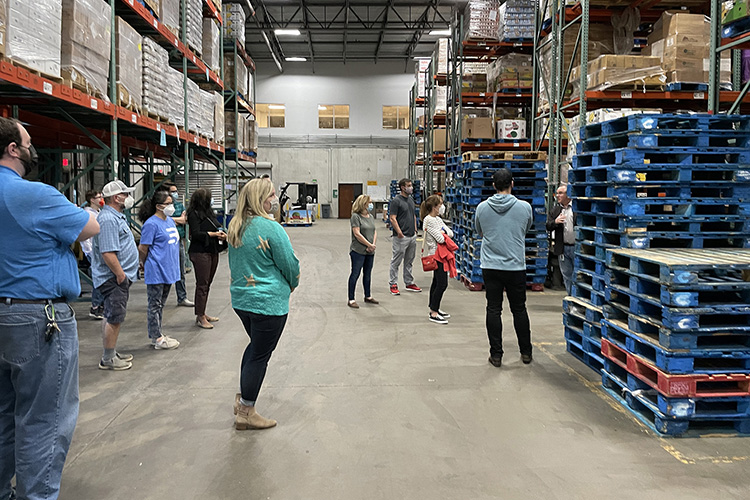 Frank Ellmo, at far right behind the blue pallets, senior director of operations at Second Harvest Food Bank of Middle Tennessee, explains the nonprofit's operations to students in the inaugural cohort in MTSU's data science graduate certificate program during the group's April 11 visit to Second Harvest's warehouse location in Nashville, Tenn. (MTSU photo by Charlie Apigian)