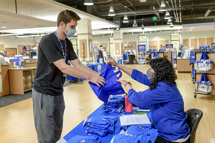 Ginger Corley, right, MTSU alumni relations director, helps graduating senior Nathan L. Smith of Unionville, Tennessee, with a bag for his cap, gown and other commencement items in Phillips Bookstore Monday, May 3. Smith, a biochemistry major whose undergrad research includes food safety and mosquito-borne diseases, plans to attend medical school after he receives his bachelor's degree in Murphy Center Saturday afternoon, May 8. MTSU's spring 2021 graduates are returning to Murphy Center May 7-9 for the first time since 2019 for a three-day, 10-event, socially distanced commencement weekend. (MTSU photo by J. Intintoli)