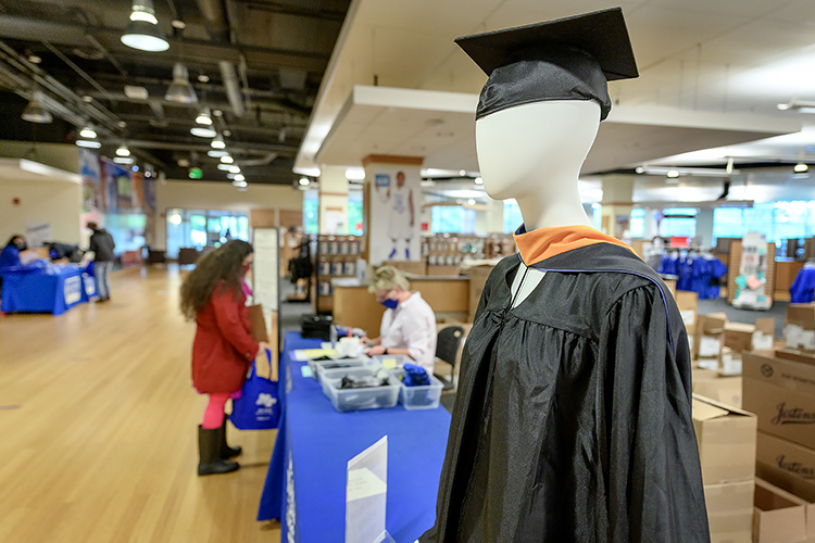 A mannequin displays the latest fashion for graduates of the MTSU School of Nursing master's program inside Phillips Bookstore Monday, May 3, as graduating students pick up their caps, gowns and other items in the background. MTSU's spring 2021 graduates are returning to Murphy Center May 7-9 for the first time since 2019 for a three-day, 10-event, socially distanced commencement weekend. (MTSU photo by J. Intintoli)