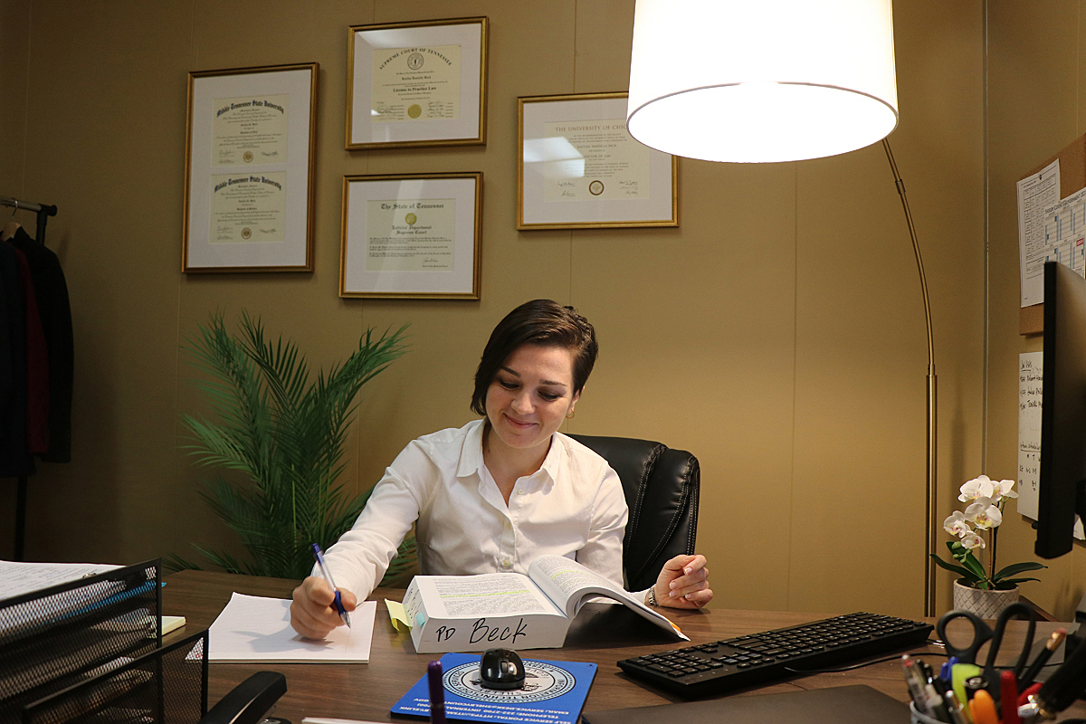 """Kaitlin Beck, an MTSU alumna and assistant public defender in the Shelby County Public Defender's Office in Memphis, researches a suppression issue related to a client's stop and arrest. Items on her office wall include framed certificates from her two MTSU bachelor's degrees (French Language and Economics), law degree, license to practice and """"Order of Admission"""" into the Tennessee Bar, permitting her to practice law in Tennessee, from the Tennessee Supreme Court. MTSU alumnus Lee Whitwell made the motion for her admission. (Submitted photo by Margaret Mahaffey)"""