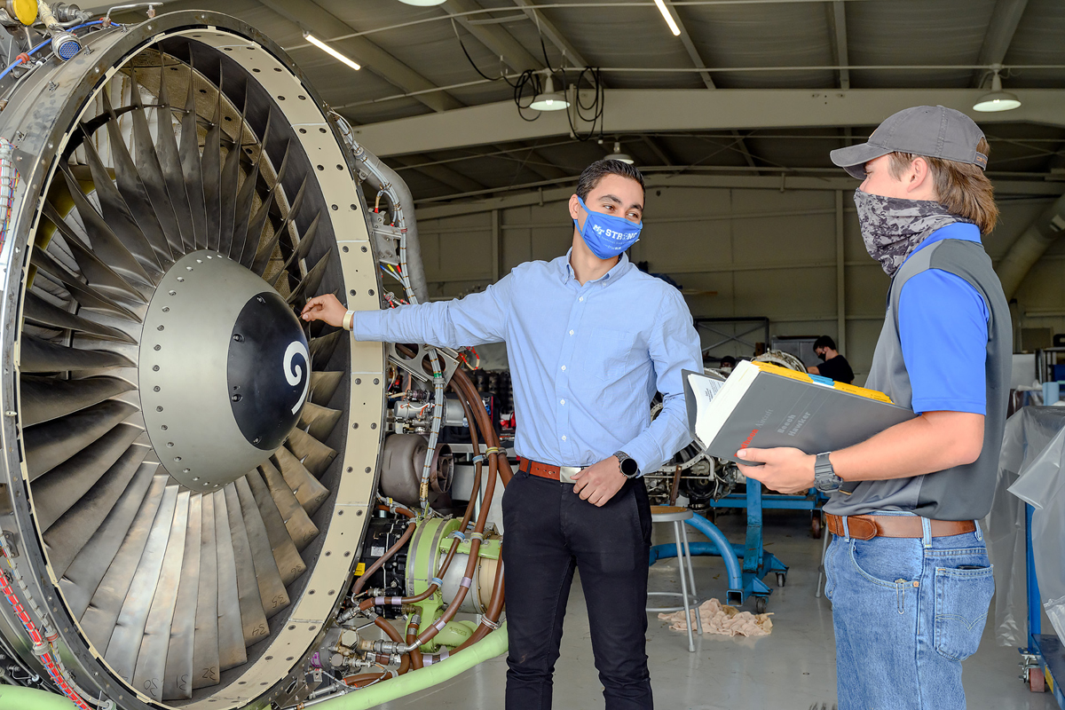MTSU seniors Wagdy Hanna, left, and Logan Knight discuss topics related to a jet engine they are training on in the Flight Operations Center maintenance hangar at Murfreesboro Airport. They are among five MTSU students who received National Business Aviation Administration Charities scholarships to attend out-of-state training for up to two weeks during the 2020-21 academic year. (MTSU photo by J. Intintoli)
