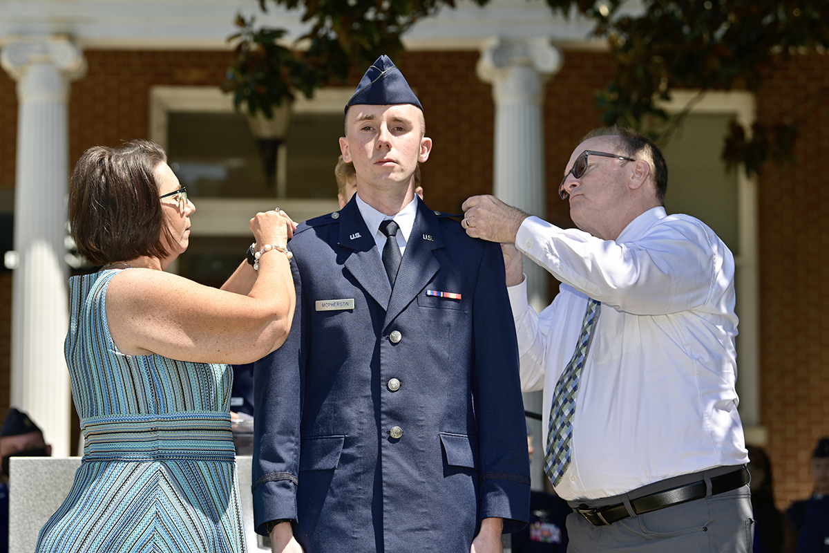 Recent MTSU aerospace professional pilot graduate Jack McPherson, center, has his U.S. Air Force second lieutenant bars placed on his uniform by his mother, Sherry McPherson, left, and father, Todd, during the Air Force ROTC Detachment 790/Tennessee State University commissioning ceremony Saturday, May 15, at the Veterans Memorial outside the Tom H. Jackson Building. Partially hidden, Ben McPherson pins the bars to his older brother's flight cap. The MTSU Daniels Veterans Center hosted the event for the detachment based at Tennessee State University. (MTSU photo by Andy Heidt)
