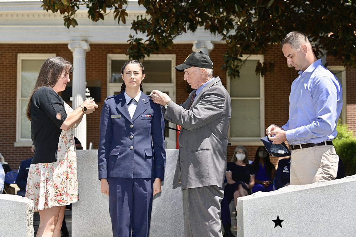 Recent MTSU aerospace aviation management graduate Kendra Pomeroy, center, has her U.S. Air Force second lieutenant bars placed on her uniform by her mother, Jean Aubin, left, of Charlotte, North Carolina, and grandfather, Larry Weidenhamer, of Tennessee, as her father, Craig Pomeroy, of Sterling, Mass., holds the bars for her flight cap during the Air Force ROTC Detachment 790/Tennessee State University spring commissioning ceremony May 15 at the Veterans Memorial outside the Tom H. Jackson Building. The event was sponsored by the Charlie and Hazel Daniels Veterans and Military Family Center. (MTSU photo by Andy Heidt)