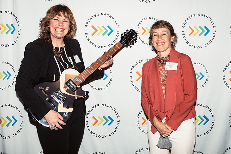 Middle Tennessee State University business intelligence and analytics professor Amy Harris, left, holds the signature guitar-themed award from the Greater Nashville Technology Council Diversity as winner of the Inclusion Advocate of the Year Award at the 12th Annual NTC Awards held in April from Stage Post Studios in Nashville, Tenn. At right is Lawrence Blank-Cook, managing director of technology at Deloitte, award sponsor. The 2021 awards ceremony was livestreamed as a hybrid in-person and virtual event. (Photo courtesy of Nathan Zucker)