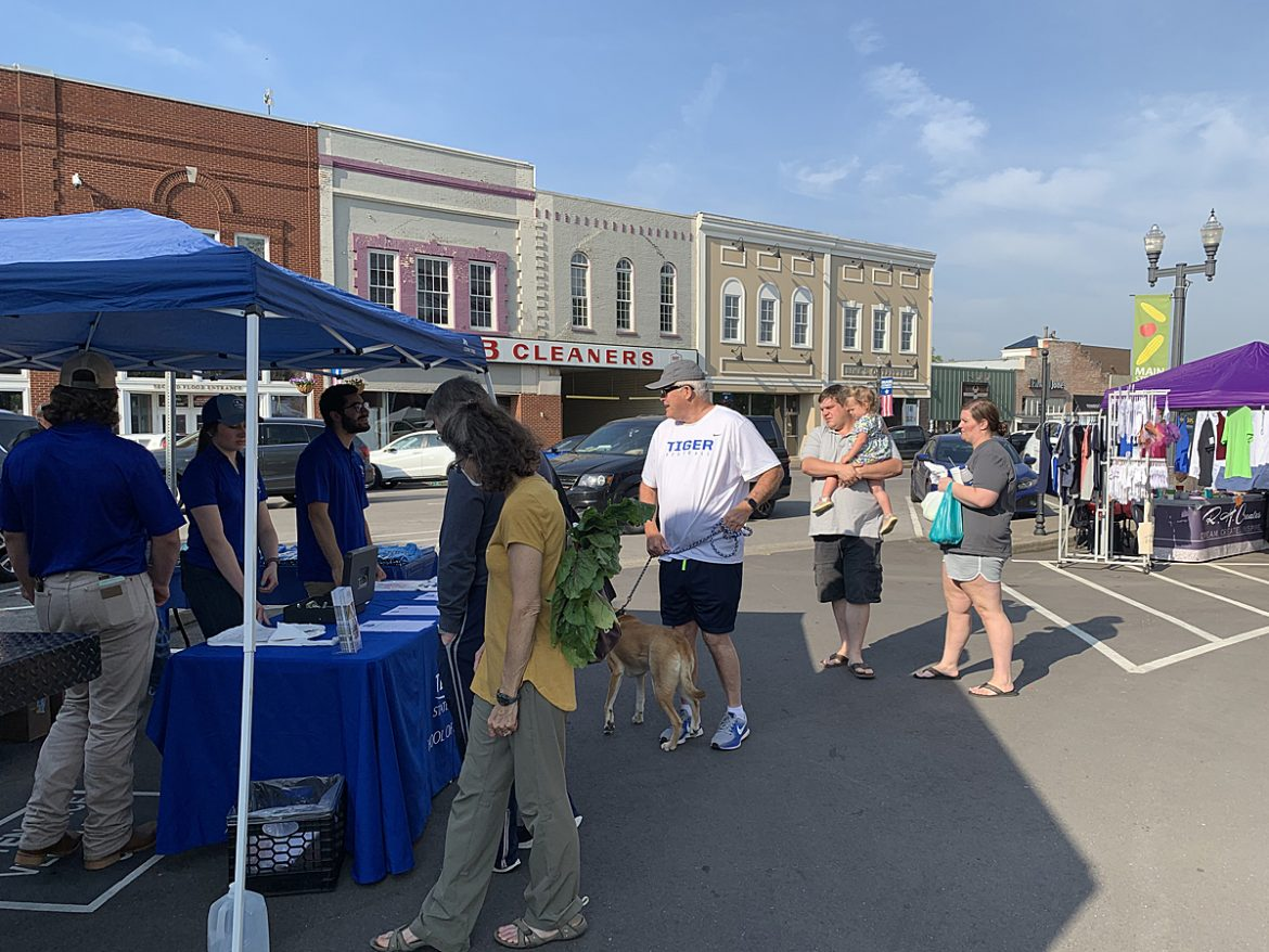 A group of people attending the first Main Street Saturday Market in 2021 line up to purchase MTSU Creamery products brought to the farmer's market at the Historic Rutherford County Courthouse Square in Murfreesboro May 22. The market, featuring MTSU milk and more than 50 other vendors selling produce, flowers, bread and more, ends Oct. 30. (MTSU photo by Randy Weiler)