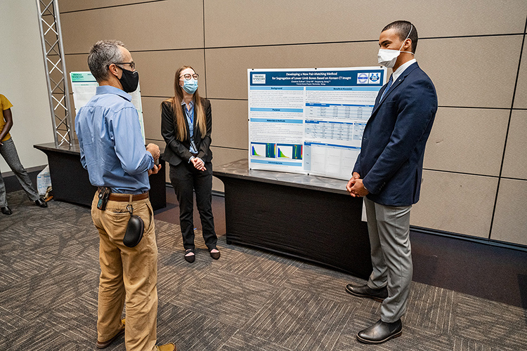 Middle Tennessee State University students Charlene Sullivan, center, and Omar Ali, right, present their research poster to Frank Bailey, left, biology professor, at the Scholars Week 2021 exposition in the Student Union Ballroom on April 16, 2021. (MTSU photo by Andy Heidt)