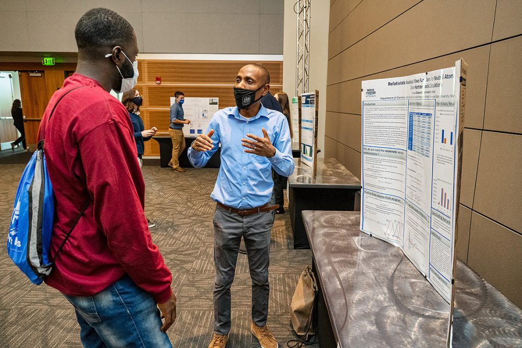 Shiroye Olukayode, right, Middle Tennessee State University student, presents his research project to fellow student Olajide Adegboyega, left, at the Scholars Week 2021 exposition in the Student Union Ballroom on April 16, 2021. (MTSU photo by Andy Heidt)