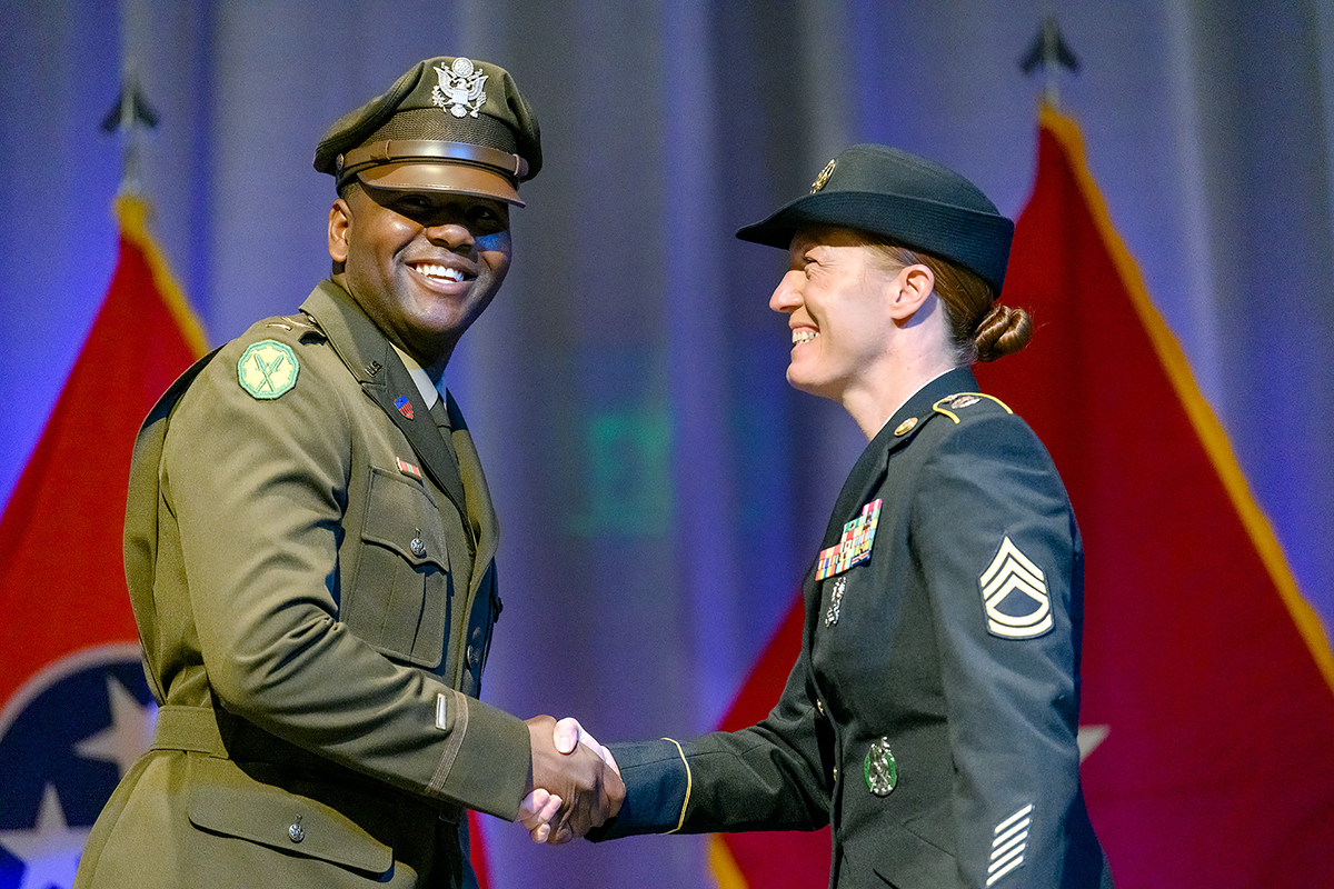Newly commissioned U.S. Army 2nd Lt. Arne Fisher, left, receives his First Salute and gives a silver dollar to Sgt. 1st Class Kathryn Rayburn during the MTSU Blue Raider Battalion Spring Commission Ceremony Friday, May 7, in the Student Union Ballroom. An Army tradition, newly commissioned second lieutenants hand a silver dollar to the first enlisted soldier who salutes them. (MTSU photo by J. Intintoli)