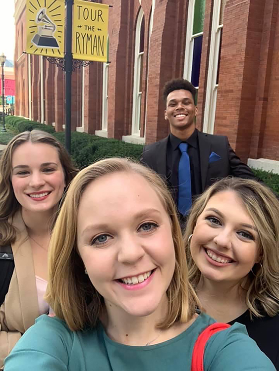 """Four members of a nine-member MTSU School of Journalism and Strategic Media student team take a break for a quick group selfie outside the Ryman Auditorium in Nashville last October while preparing their national award-winning 30-minute TV and web special, """"100 Years of Broadcasting."""" Clockwise from front, they are senior journalism major Cheyana Avilla of Murfreesboro; May 2021 journalism graduates Zoë Haggard of Nolensville, Tenn., and Dontae Rucker of Knoxville; and fall 2020 graduate Christyn Allen of Oneida, Tenn. (photo submitted)"""