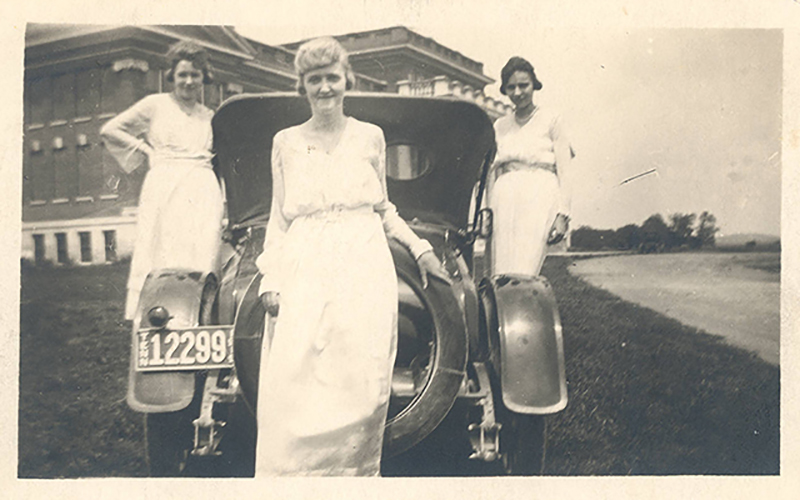 """Three female students at then-Middle Tennessee State Normal School pose by a shiny roadster near the southwest corner of Kirksey Old Main in this 1920s-era photo from the Alumni Collection of MTSU's Albert Gore Research Center. The College of Liberal Arts and MTSU Alumni Association are inviting alumni and university neighbors to join a """"Roaring Twenties""""-themed free online """"Lifelong Learning"""" program discussion of life in France, American musicals, and Prohibition in Tennessee and the United States on Tuesday, May 11. (Photo courtesy of the Albert Gore Research Center at MTSU)"""