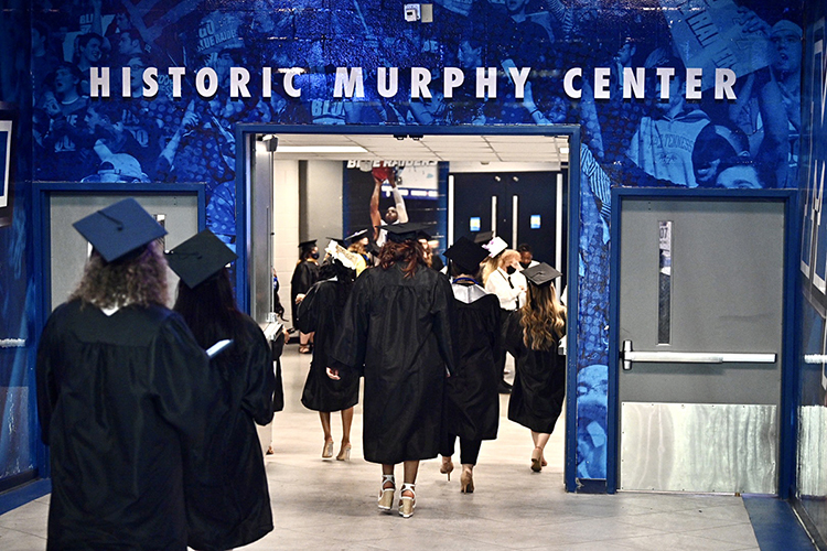 Members of MTSU's first Class of 2021 walk down a hallway under Murphy Center to take their seats in Hale Arena before one of the three spring 2021 commencement ceremonies held Friday, May 7, inside the facility. Graduates and their guests returned to Murphy Center May 7-9 for the first time since 2019 for a three-day, 10-event, socially distanced commencement weekend. (MTSU photo by J. Intintoli)