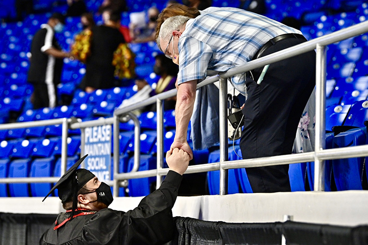 A graduating MTSU student clasps hands with an audience member at the College of Liberal Arts commencement in MTSU's Murphy Center Friday, May 7, during the first day of the university's spring 2021 commencement ceremonies. Students returned to Murphy Center May 7-9 for the first time since 2019 for a three-day, 10-event, socially distanced commencement weekend. (MTSU photo by J. Intintoli)