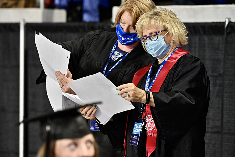 """MTSU commencement heralds Allison McGoffin, left, and Pat Thomas, wearing their masks and """"Team Grad"""" ID badges, check their seating charts Friday, May 7, inside Murphy Center to ensure that the spring 2021 graduates are in the correct order when their names are called to cross the stage. McGoffin, assistant to University Provost Mark Byrnes, and Thomas, assistant to the university's Board of Trustees and to retired Lt. Gen. Keith M. Huber, senior adviser for veterans and leadership Initiatives, are members of a well-practiced crew helping students returning to Murphy Center May 7-9 for the first time since 2019 for a three-day, 10-event, socially distanced commencement weekend. (MTSU photo by J. Intintoli)"""