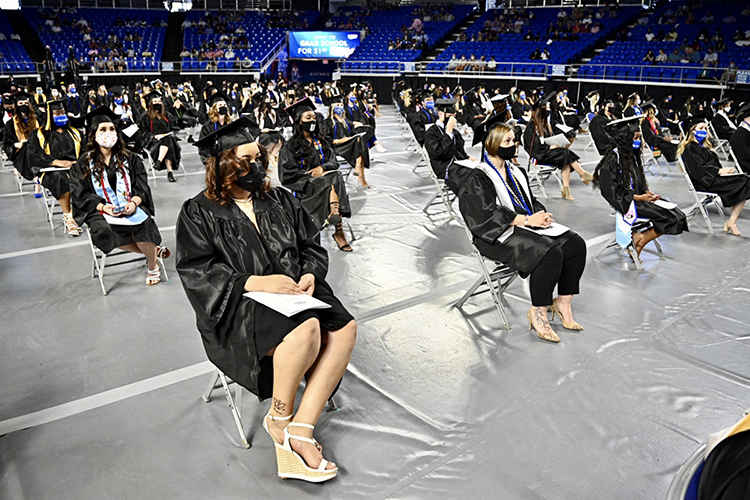 Members of MTSU's first Class of 2021 sit, masked and 6 feet apart, on the floor of Hale Arena in Murphy Center Friday, May 7, as they prepare to graduate during the first day of the university's spring 2021 commencement ceremonies. Students returned to Murphy Center May 7-9 for the first time since 2019 for a three-day, 10-event, socially distanced commencement weekend. (MTSU photo by J. Intintoli)