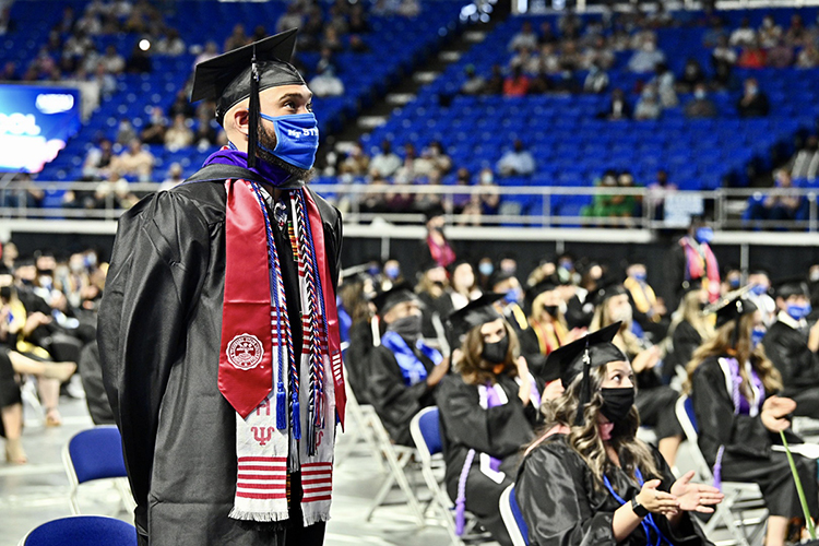 A graduating student-veteran, wearing a special red stole designating his military service, stands inside MTSU's Murphy Center as he and other service members are recognized Friday, May 7, during the first day of the university's spring 2021 commencement ceremonies. Students returned to Murphy Center May 7-9 for the first time since 2019 for a three-day, 10-event, socially distanced commencement weekend. (MTSU photo by J. Intintoli)