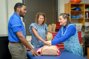 Service to students portrait of Athletic Training faculty Kristi Phillips and Helen Binkley working with student Nick Smith.