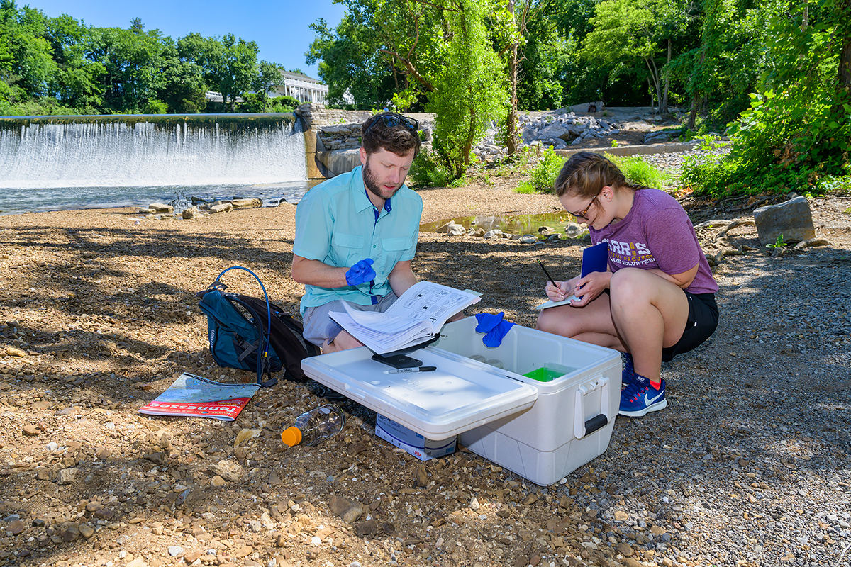 MTSU biology research assistant professor Cole Easson, left, and rising senior Jacqueline Williams of Drummonds, Tenn., check the reading a special pump that will provide data from their Stones River Watershed project that officially begins July and ends next spring when Williams writes her Honors College thesis and presents and one or more conferences. They will map aquatic diversity using next-generation sequencing techniques relative to land use in the surface waters in the river. (MTSU photo by Andy Heidt)