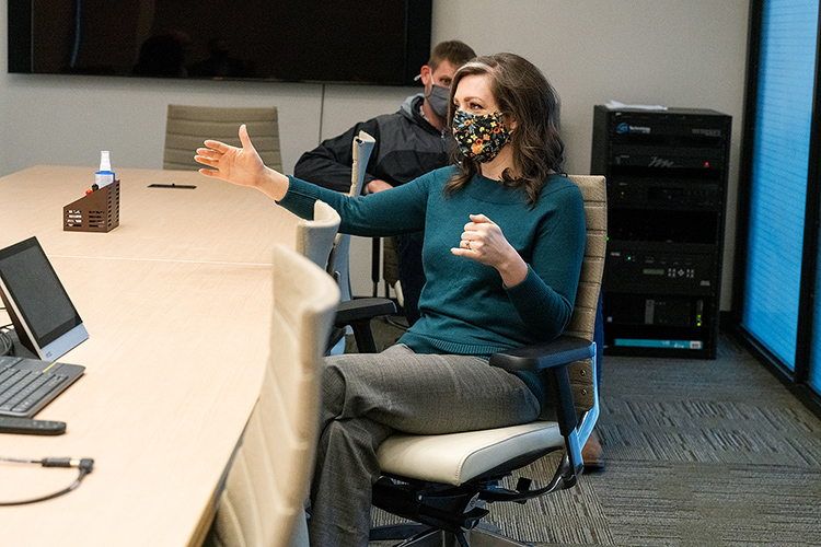 Tiffany Rogers, a Middle Tennessee State University assistant professor of psychology, talks with peers, including fellow MTSU assistant professor Blake Whitman from the School of Concrete and Construction Management in the background, in a conference room of the Science Building on campus on March 31, 2021. (MTSU photo by Andy Heidt)