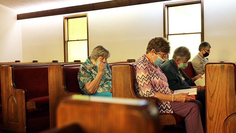 """The four members of Tate's Chapel United Methodist Church in Chilhowie, Va., study their hymnals during a May 23 church service. The tiny congregation, reduced to four by years of relocations, retirements and deaths, received an unexpected $700,000 windfall from a former member's estate this year to do good works. Students from MTSU journalism professor Leon Alligood's summer 2021 """"Road Trip"""" feature writing class trip to Bristol, Tenn., were the first to report on the church's news. (photo courtesy of Jordan Cobbs)"""