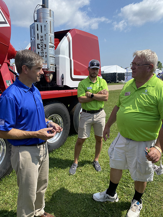 Greg Van Patten, left, interim dean of the MTSU College of Basic and Applied Sciences, meets with officials with the Oshkosh Corp. on behalf of MTSU's School of Concrete and Construction Management on the grounds of the EAA AirVenture 2021, which runs July 26-Aug. 1 in Oshkosh, Wisc. The corporation, which makes concrete trucks and other heavy equipment, had a presence at EAA. (MTSU photo by Andrew Oppmann)