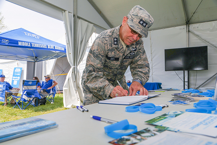 Maj. Gen. Mark Smith, Civil Air Patrol's national commander and chief executive officer, signs the guest book Monday, July 26, at Middle Tennessee State University's Aerospace Department booth on the grounds of the EAA AirVenture 2021 happening all week in Oshkosh, Wisc. (U.S. Air Force Auxiliary photo by Lt. Col. Robert Bowden)