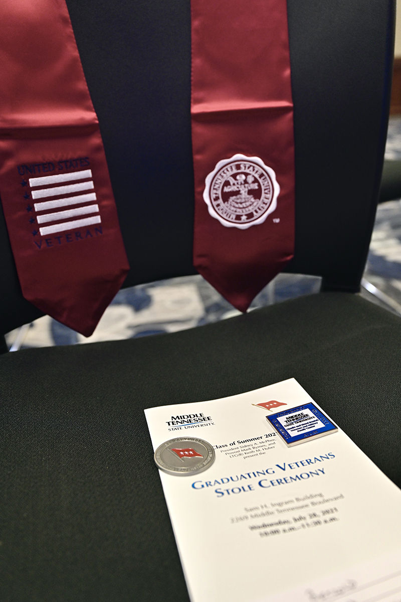 A red stole to wear at graduation and a special coin and pin are shown with the program for the MTSU Daniels Center Graduating Veterans Stole Ceremony Wednesday, July 28, in the Ingram Building. The honorees will graduate Saturday, Aug. 7, in Murphy Center. (MTSU photo by Andy Heidt)